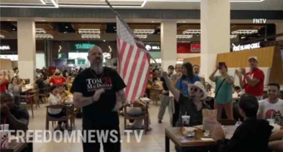 """Activistas coreando """"Que se pudra Estados Unidos """" y """"Joe Biden"""" entran en un patio de comidas autorizado '' solo para vacunados'' en Nueva York, en protesta contra los mandatos obligatorios"""